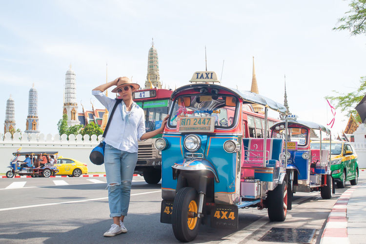 BANGKOK, THAILAND - April 16, 2019: Landmark, Wat Phra Kaew, Tuk Tuk signature of Thailand Bangkok Bangkok Thailand. Summer Holiday Colorful Vacation Architecture City One Person Full Length Built Structure Mode Of Transportation Transportation Real People Building Exterior Young Adult Lifestyles Casual Clothing Travel Car Leisure Activity Day Motor Vehicle Sky Front View Outdoors Human Arm City Street Taxi Visiting