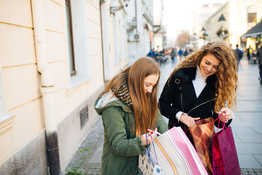 Two young attractive women look at shopping bags Boutique Business Sale Shopping Standing Buying Consumerism Customer  Gift Hair Leisure Activity Lifestyles Outdoors Positive Emotion Real People Retail  Santas Hat Shopaholic Shopping Bag Shopping Mall Store Street Two People Young Adult Young Women