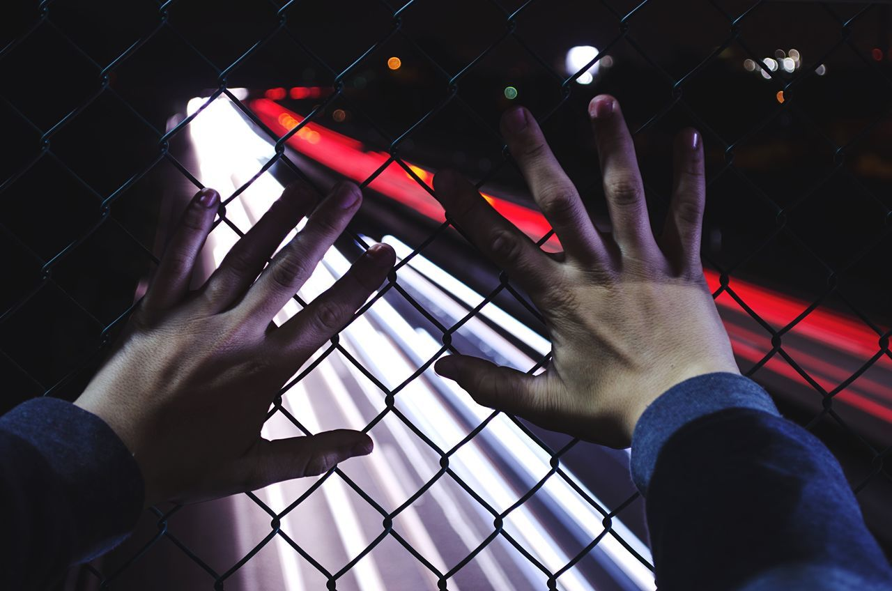 Cropped image of hands on chainlink fence against illuminated light trails