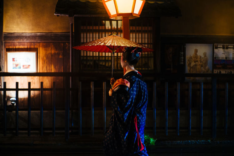 Full length of woman standing against illuminated building
