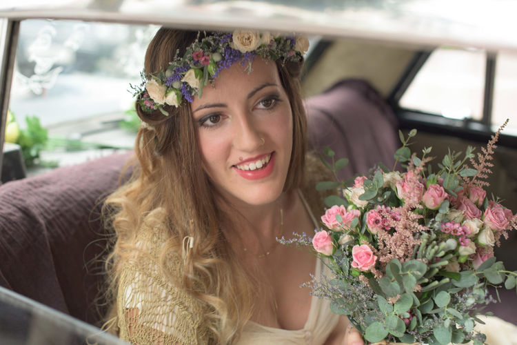 Smiling bride with flower bouquet sitting in car