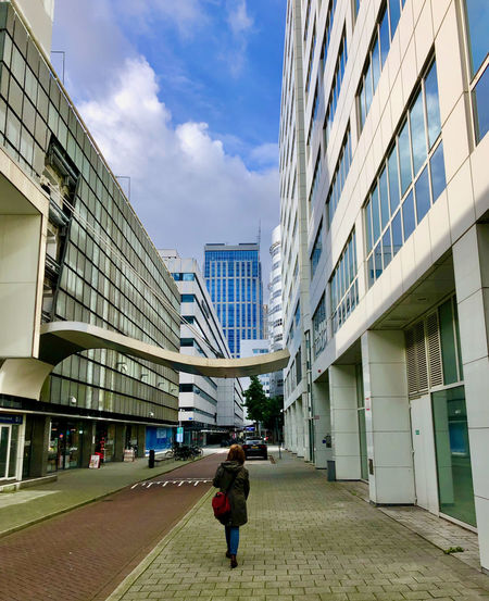 Rear view of woman walking on footpath amidst buildings in city