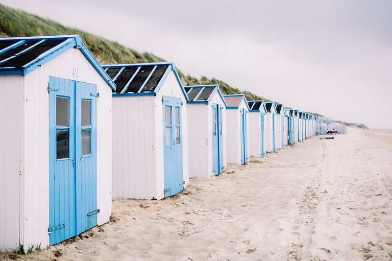 Huts In Row At Sandy Beach Against Sky