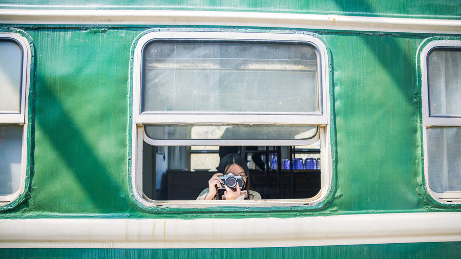 Woman photographing while traveling in train