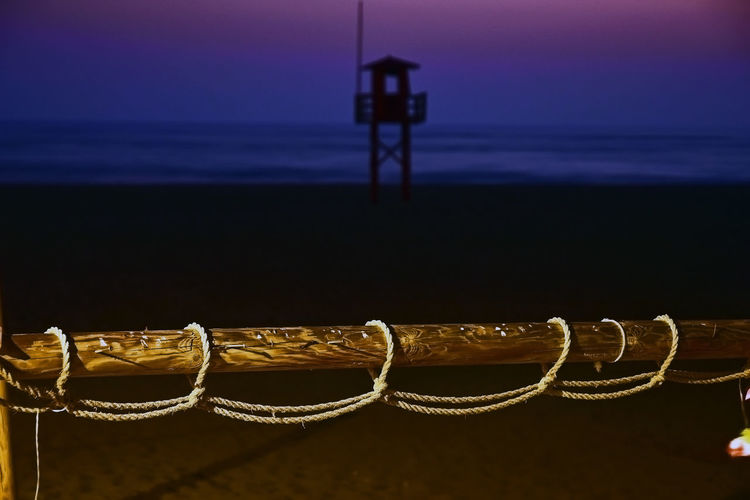 Close-up of rope against sea during sunset