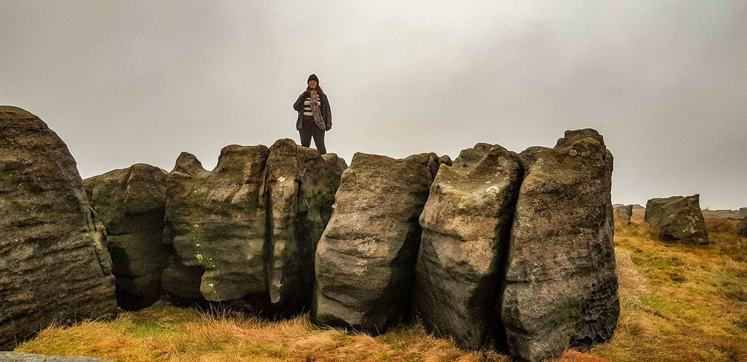 Woman standing on rock against sky