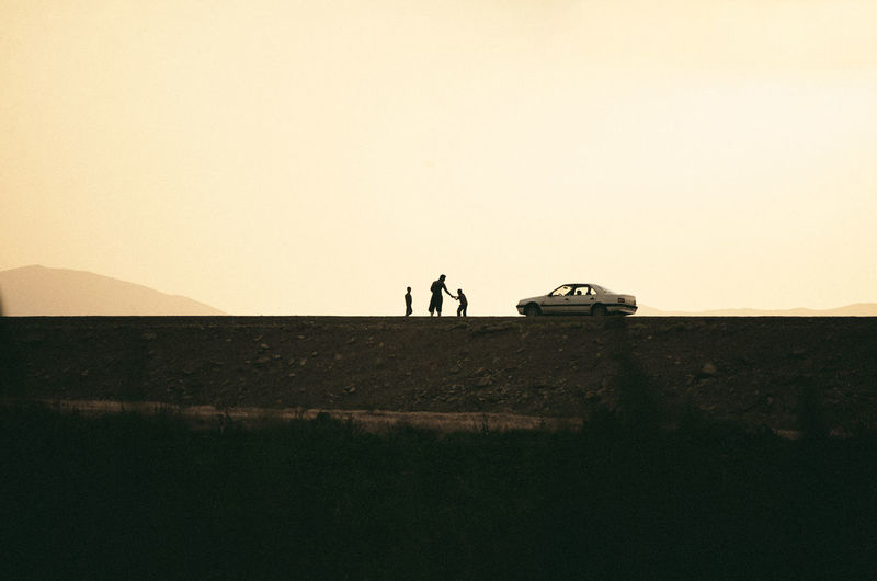 Silhouette of man and boys standing by car against sky during sunset