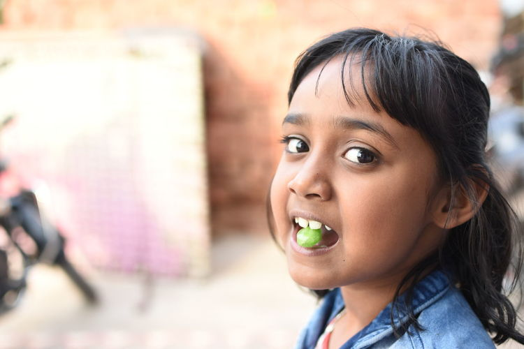 Close-up portrait of girl eating candy