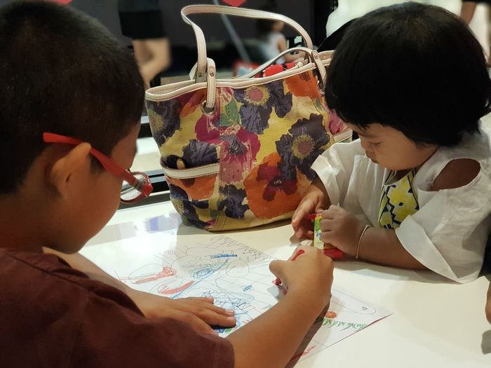 Boy with sister drawing on paper at table