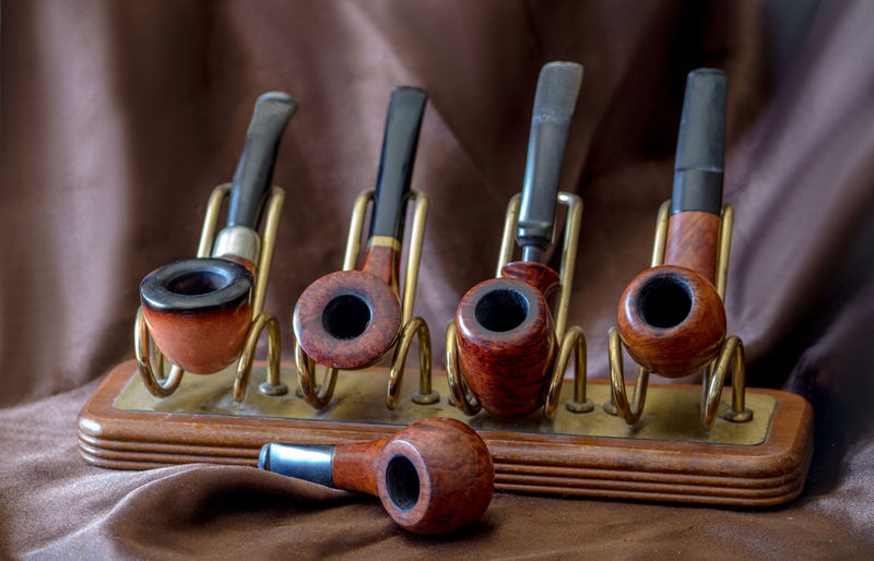 Close-up of smoking pipes on brown fabric