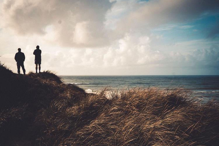 Scenic view of sea with men standing on grass against sky