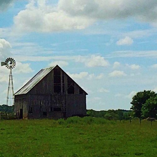 Barn on grassy field against cloudy sky