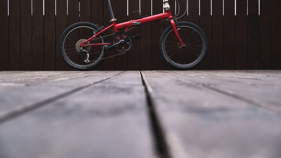 Bicycle parked on footpath against wall