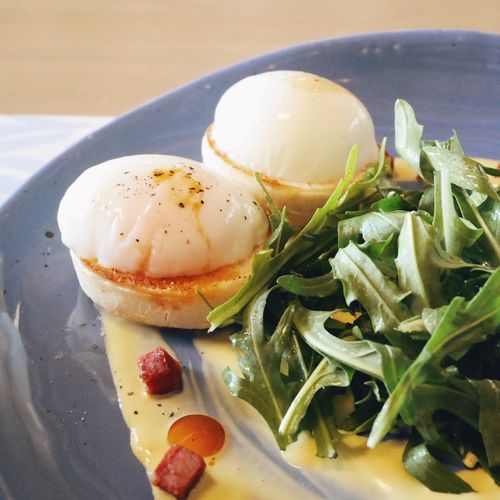Close-up of eggs benedict and arugula in plate