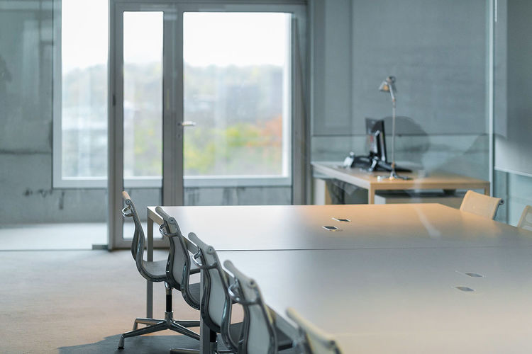 Empty chair by table in conference room