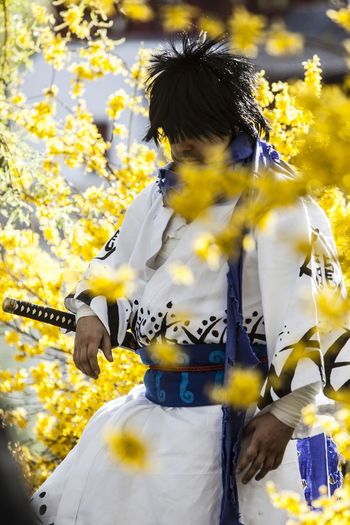 Man wearing samurai costume standing amidst yellow flowers at park