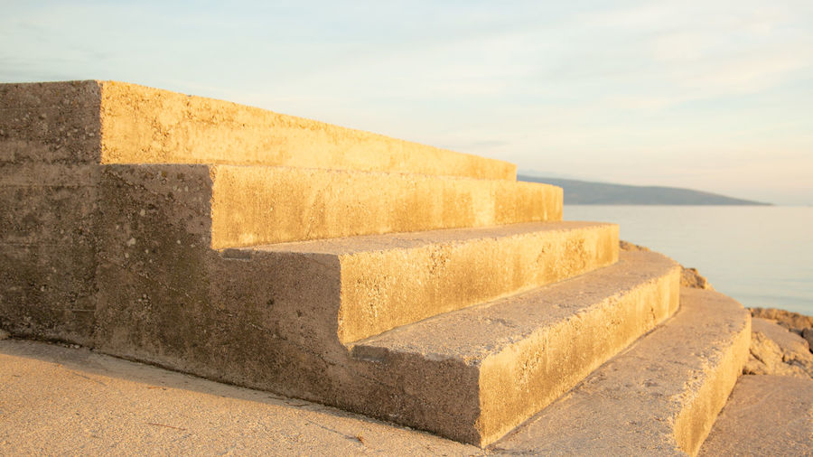 Close-up of concrete wall with sea in background