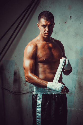 Muscular Build Strength Shirtless Healthy Lifestyle Three Quarter Length Indoors  Lifestyles Standing Athlete Exercising One Person Young Men Sport Sports Training Young Adult Men Wall - Building Feature Real People Wellbeing Weight Training