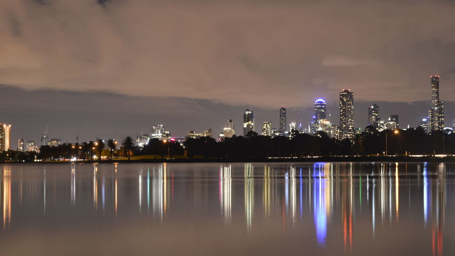 Albert Park Lake By Illuminated Buildings Against Cloudy Sky At Night