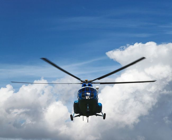 Low Angle View Of Helicopter Flying In Cloudy Sky