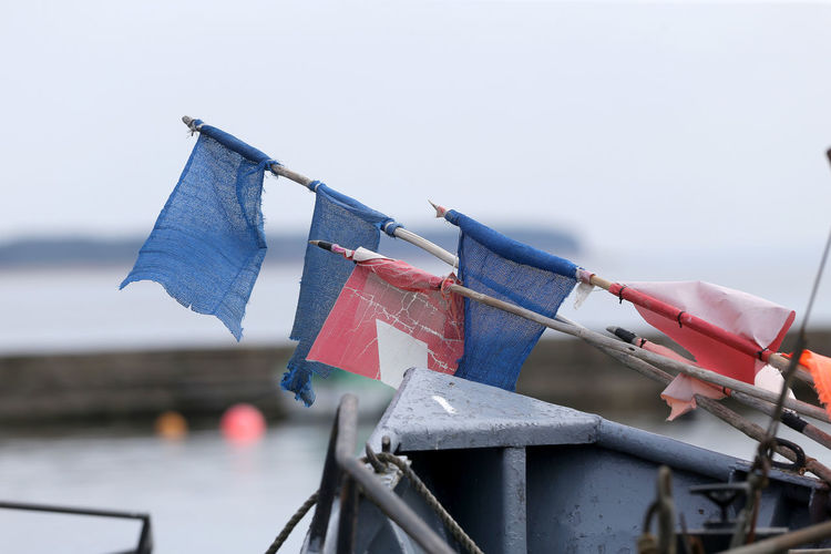 Close-up of flags against sky during rainy season