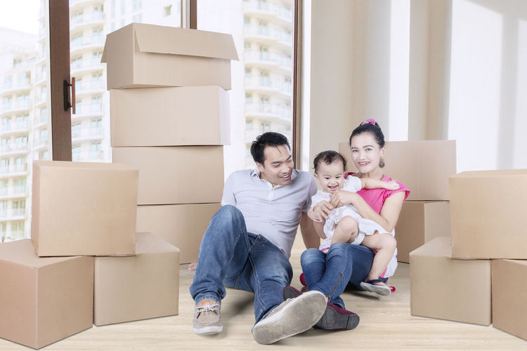 Adult Box Box - Container Cardboard Cardboard Box Casual Clothing Change Childhood Container Emotion Front View Full Length Happiness Home Ownership Indoors  Lifestyles Moving House Packing Sitting Smiling Togetherness Women Young Adult