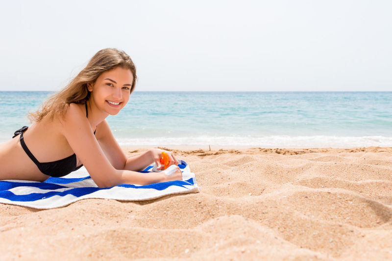Portrait of smiling woman holding sunscreen bottle while lying on towel at beach