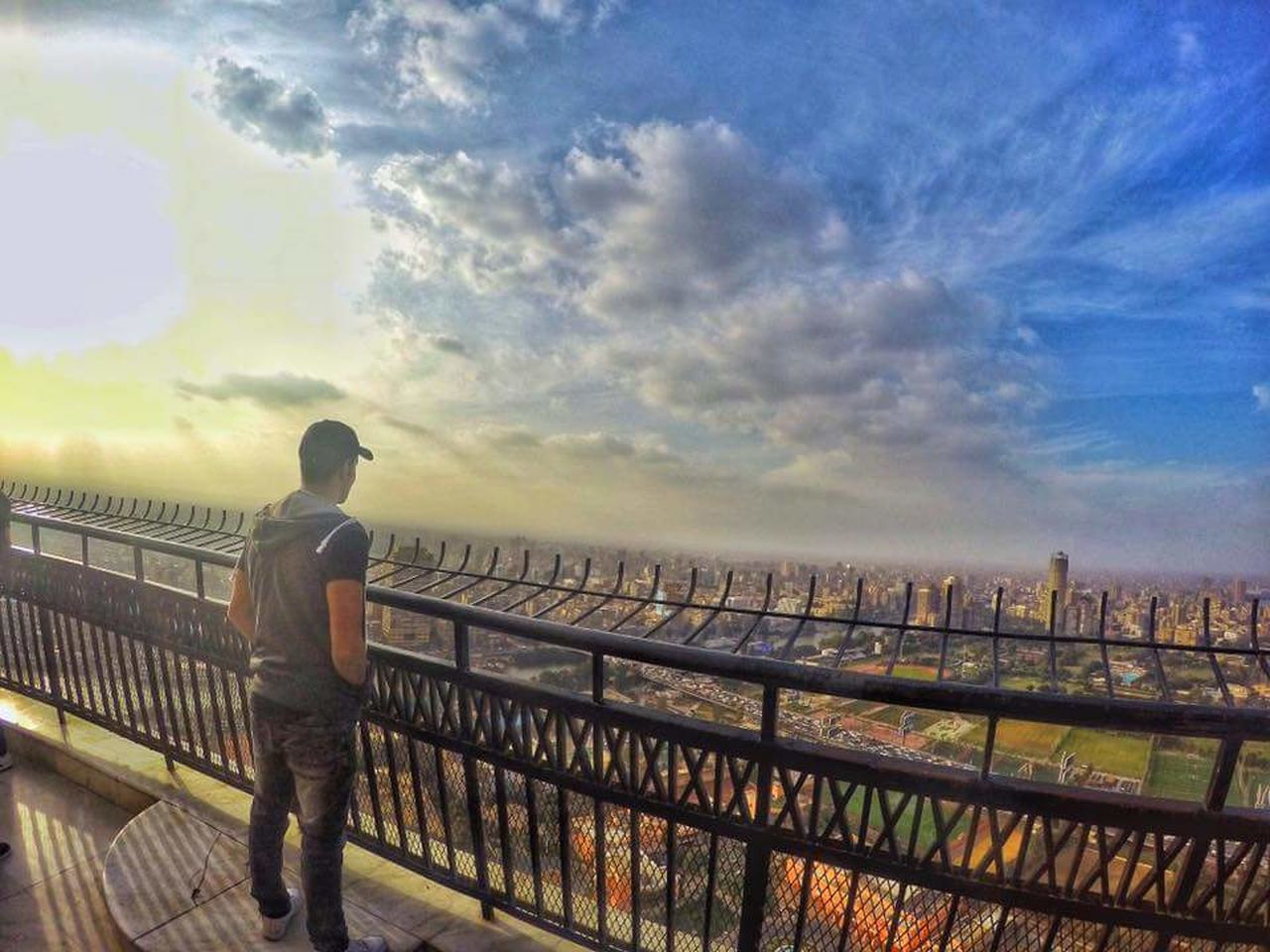 railing, sky, cloud - sky, one person, real people, full length, men, outdoors, rear view, leisure activity, standing, bridge - man made structure, lifestyles, nature, sunset, day, one man only, architecture, cityscape, adult, beauty in nature, city, only men, young adult, adults only, people