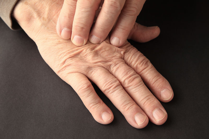 Cropped image of senior man pressing hand