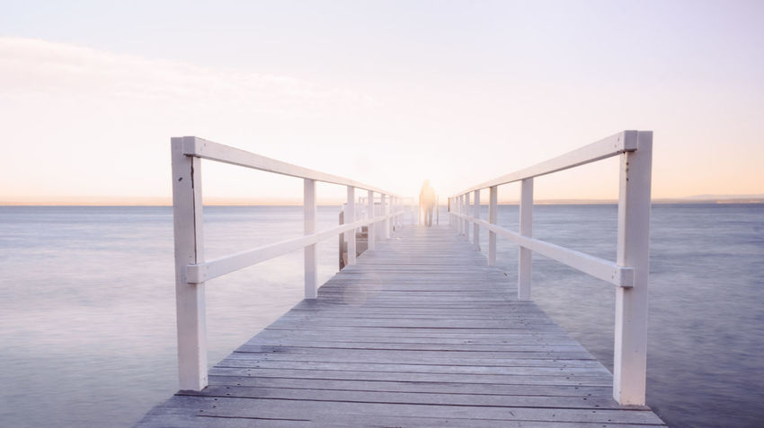 life makes ghosts of us all in the end One Woman Only One Person Minimalism EyeEm Selects Water Sea Beach Sunset Horizon Fog Bridge - Man Made Structure Sand Summer Wood - Material Boardwalk Seascape Tide Coast Railing Wood Paneling Coastal Feature Coastline Diminishing Perspective