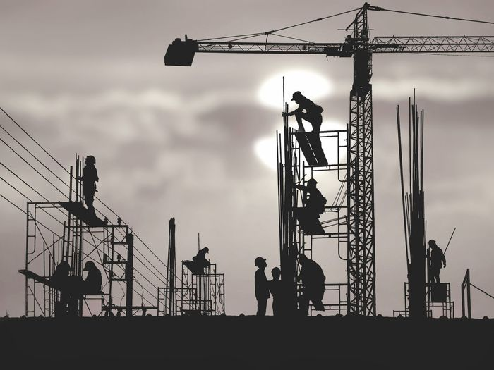 Silhouette of people at construction site against sky