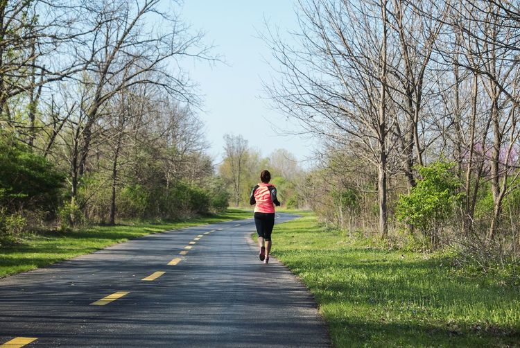 Rear view of woman running on road amidst bare trees