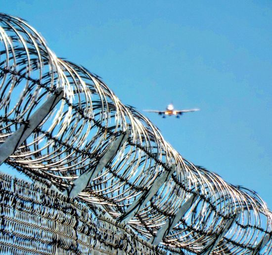 Low angle view of plane landing against clear blue sky with barbed wire fence