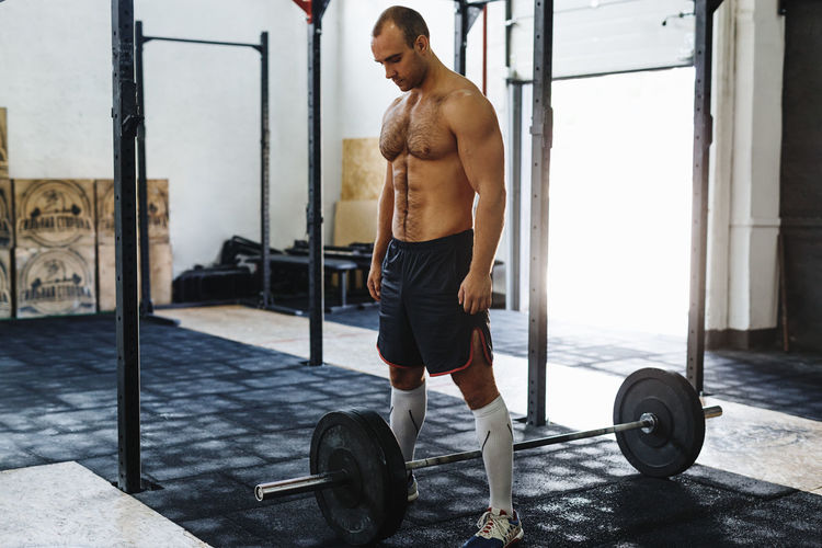 Full length of shirtless young man with barbell in gym