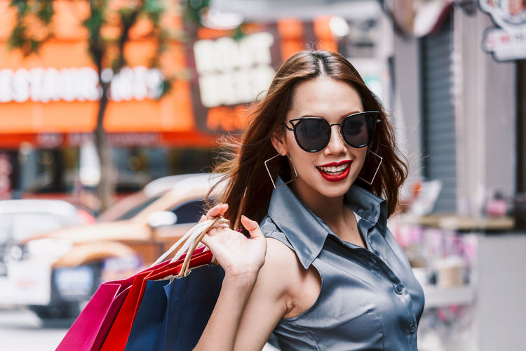 Portrait of smiling young woman with shopping bags standing on footpath