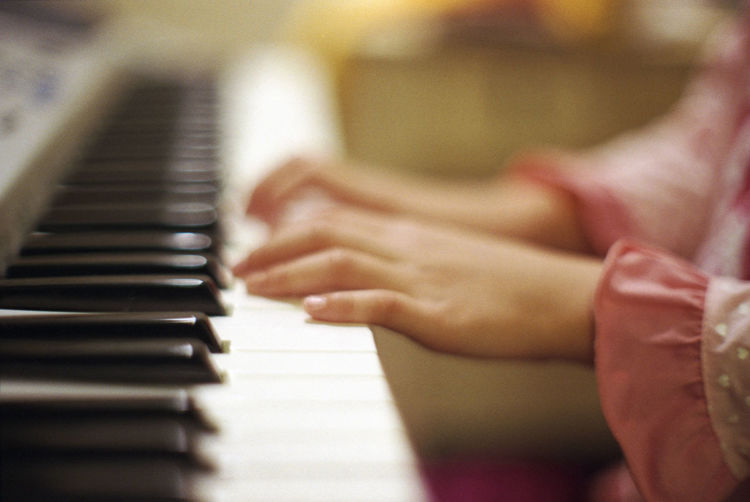 Close-up of hands playing piano