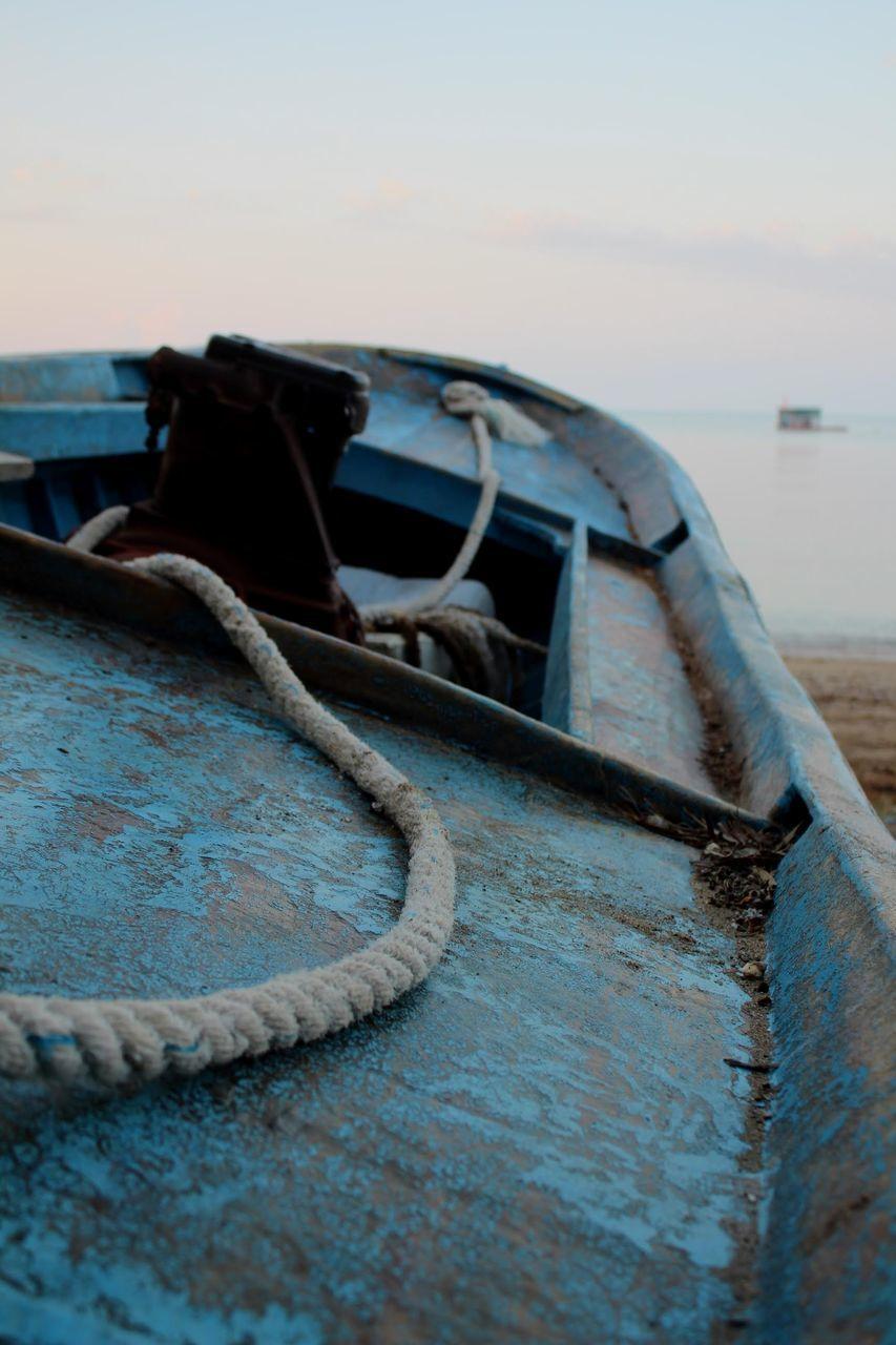 ABANDONED BOAT MOORED AT BEACH