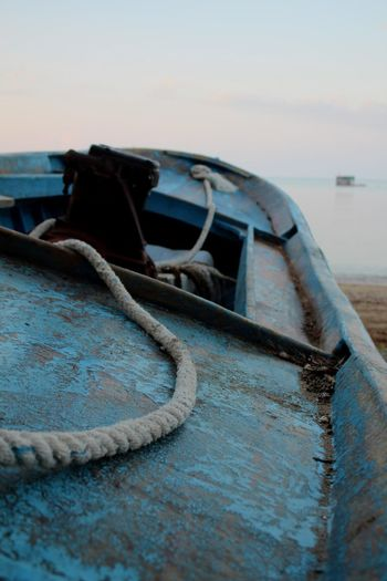 Abandoned boat moored at shore against sky