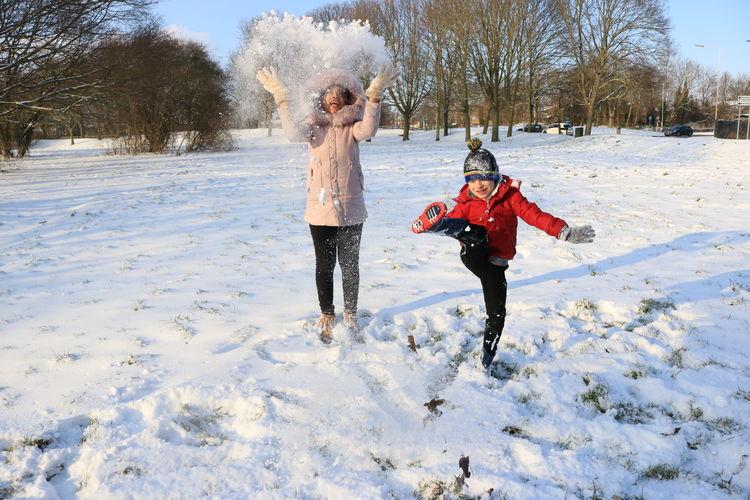 Full length of siblings playing in snow