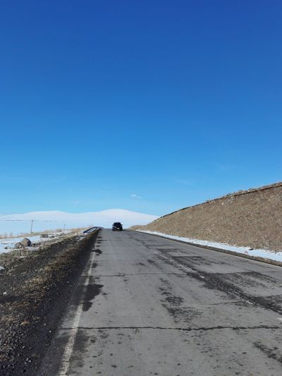 Surface level of road against clear blue sky