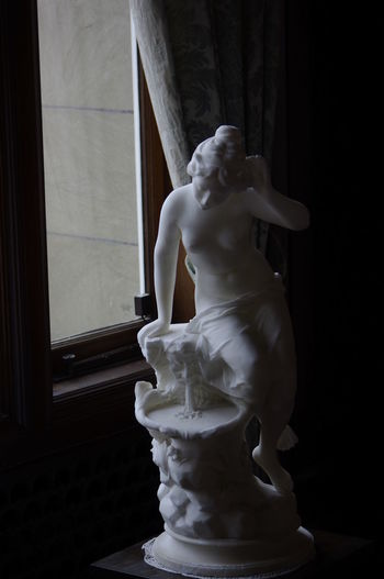 Statue by window in darkroom