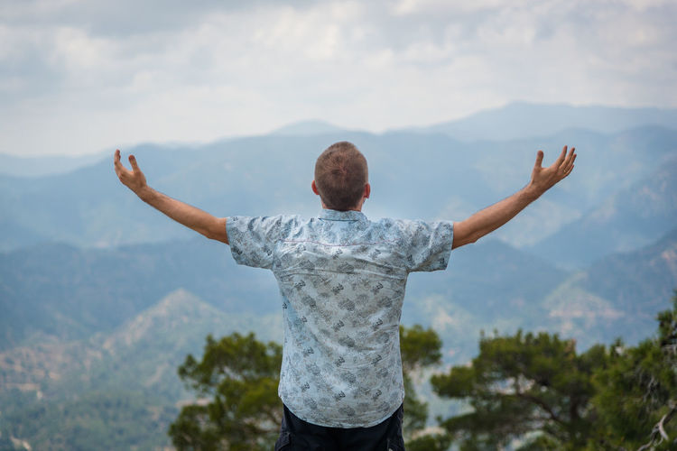Rear view of man with arms outstretched against mountain range