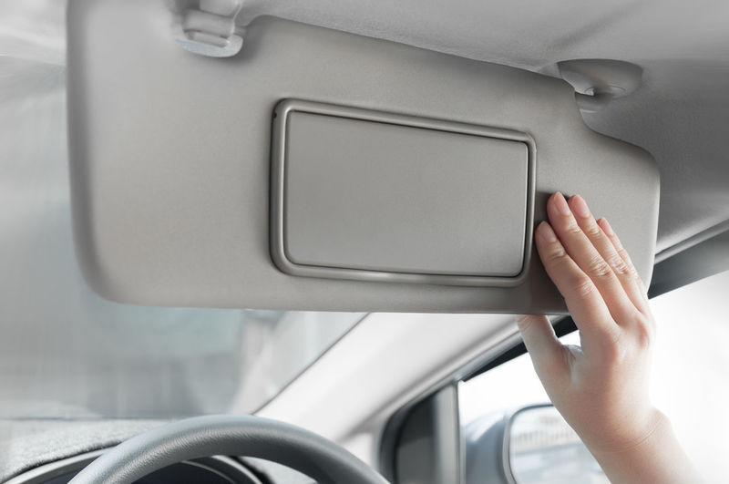 Cropped hand of woman holding sun visor in car