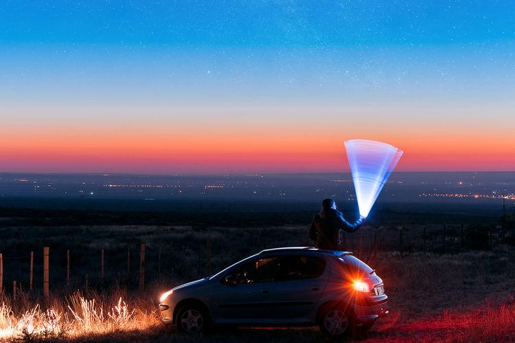 Car on illuminated field against sky at night