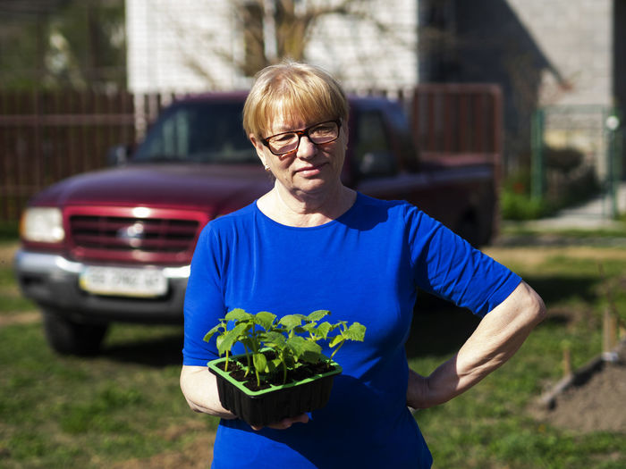 Senior caucasian woman is holds a container with cucumber seedlings. Seedlings Senior Women Caucasian Holds Container Cucumber Glasses Front View Eyeglasses  One Person Real People Focus On Foreground Waist Up Lifestyles Day Casual Clothing Plant Standing Nature Young Adult Three Quarter Length Holding Looking At Camera Adult Outdoors Hairstyle