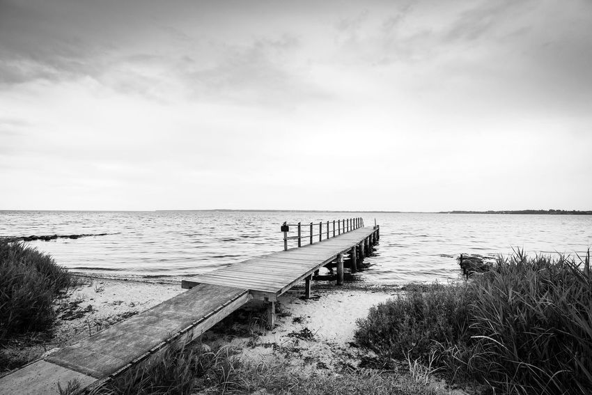Black and white photo of a pier by the shore on the sea Jetty Pier Water Sky Sea Horizon Horizon Over Water Beach Scenics - Nature Tranquil Scene Lifestyles Group Of People Cloud - Sky Beauty In Nature Real People Nature Land Day Outdoors Tranquility Leisure Activity