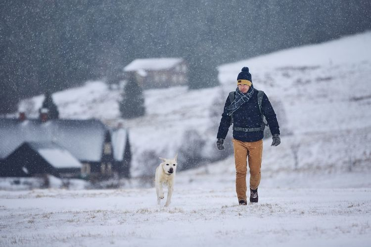Side view of man playing with dog on field during snowfall