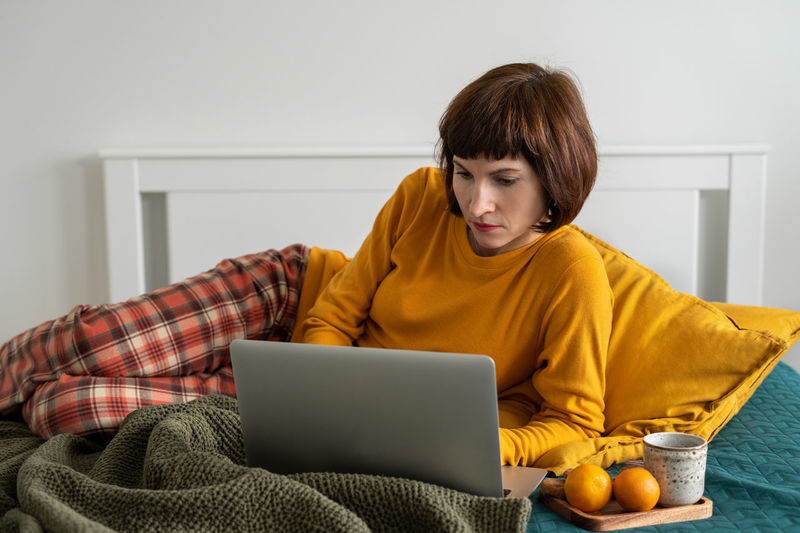 Smiling woman using laptop while sitting on bed at home