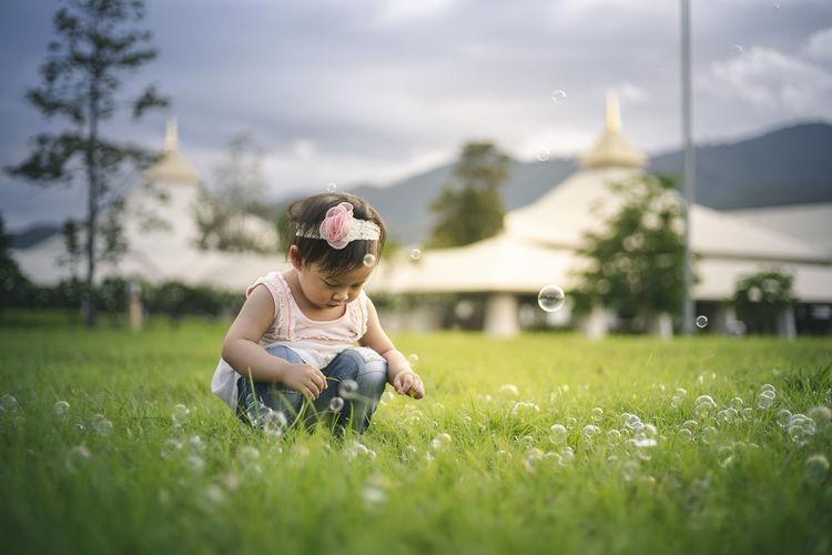 Baby girl crouching on grassy land