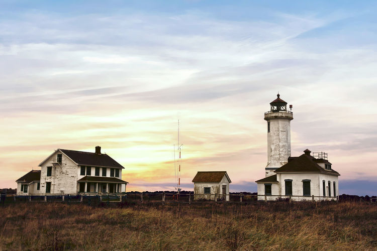 Lighthouse by building against sky at sunset